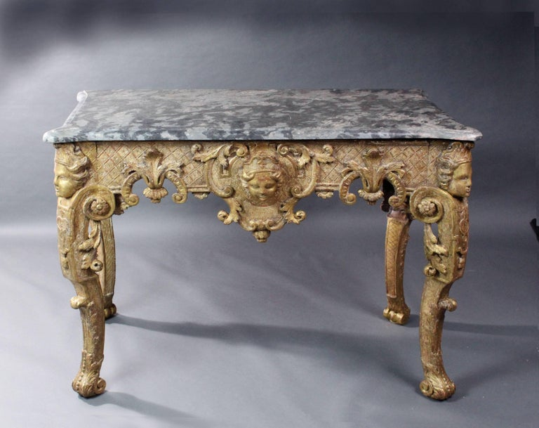 A fine late 17th-early 18th century Italian or French gilt wood console table retaining much of its original gilding; supported on well carved caryatids with scroll feet; the frieze with carved acanthus leaves, Rococo scrolls and a carved mask on a