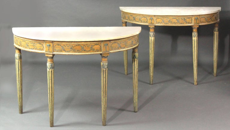 A pair of late 18th century Italian side or console tables still in their original paint: of an elliptical shape with neoclassical decoration of flowers and urns in two shades of blue on ochre and yellow grounds; the fluted legs with carved acanthus