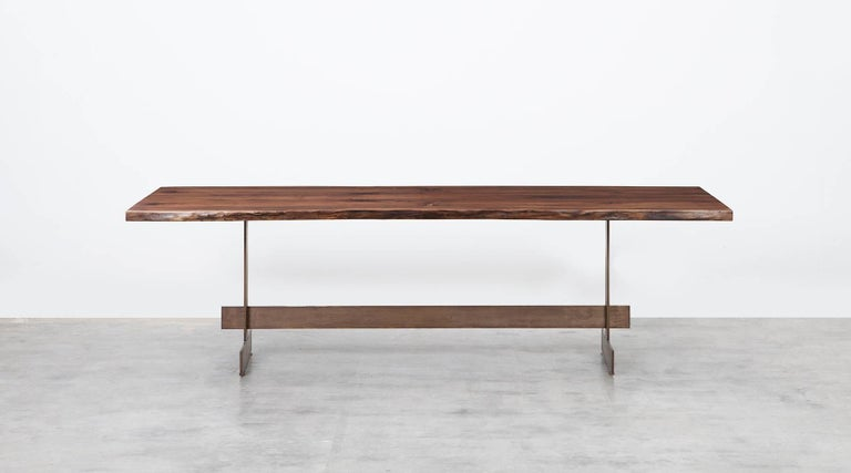 Table by contemporary German artist Johannes Hock. The shape is inspired by an originally monastery table consisting of trestle and plate. Live edge claro walnut slab resting on a blackened bronze base. Solid in material and function, reduced and