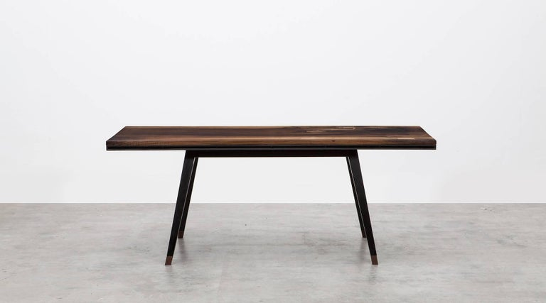 Desk by contemporary German artist Johannes Hock. This European walnut slab table top rests on a blackened oak base. Defects were replaced by wooden inlays. At the front there is a narrow storage compartment for utensils. Manufactured by Atelier
