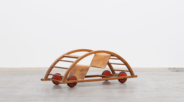 Swing cart, children toy in lacquered red wood and metal, Germany, 1951.