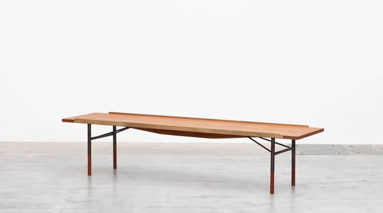 This design was conceived by Finn Juhl to be used as a bench and/or coffee table. The top surface is flanked by two solid brass strips that would have kept cushions in place but also guard against items on the surface falling off. The legs are