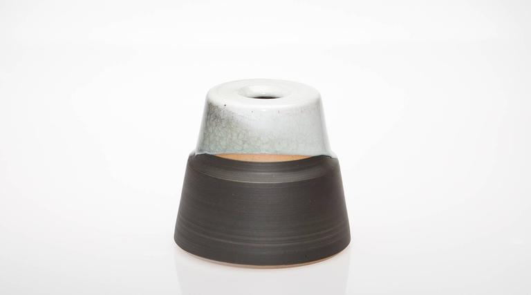 Nicely shaped, two-colored vase designed and produced by German artist Martin Schlotz. Martin Schlotz works in thematic series. In variations of a certain type of shape: Exactly twisted, robust tower forms from stoneware clay on a broad footprint,