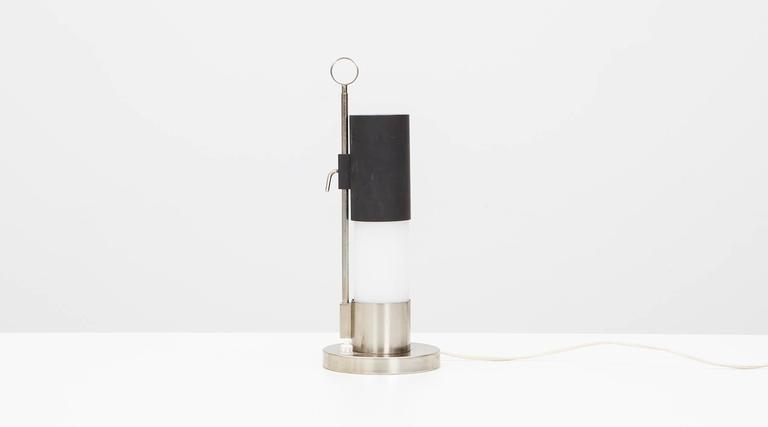 Adjustable table lamp with constructivist form is attributed to Italian designer Angelo Lelli. The cylindrical steel table lamp with sliding cover-bulb on a small steel vertical arm on a circular steel base. Manufactured by Arredoluce.