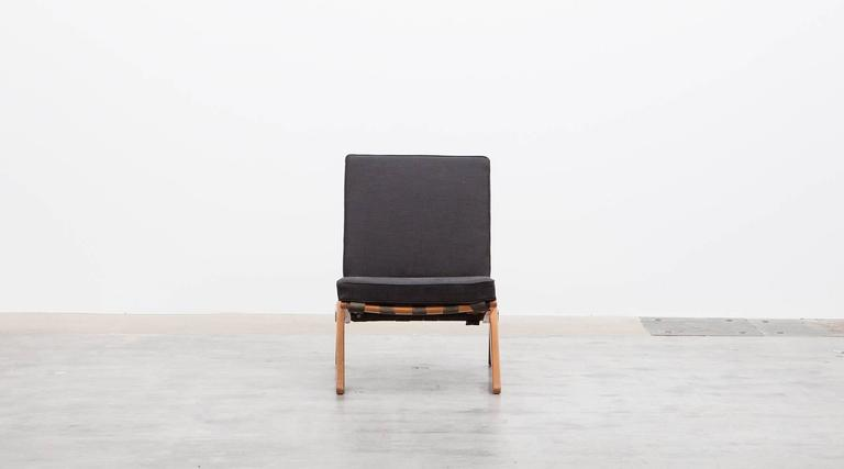 A beautiful pair of Pierre Jeanneret easy chair from 1952. The frame has a scissors-like shape, very minimalistic and unique. The cushions are recently new upholstered with high-quality fabric and give a perfect contrast to the warm wooden frame. As