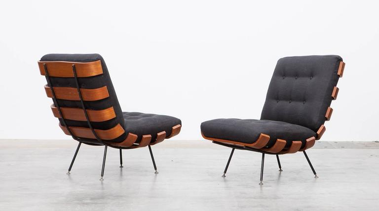 Wonderful Brazilian lounge chairs designed by Martin Eisler and Carlo Hauner. This pair has been produced in teak and plywood slats bent elegant to the ends and stands on a black lacquered metal frame with brass feet. The cushions are recently newly