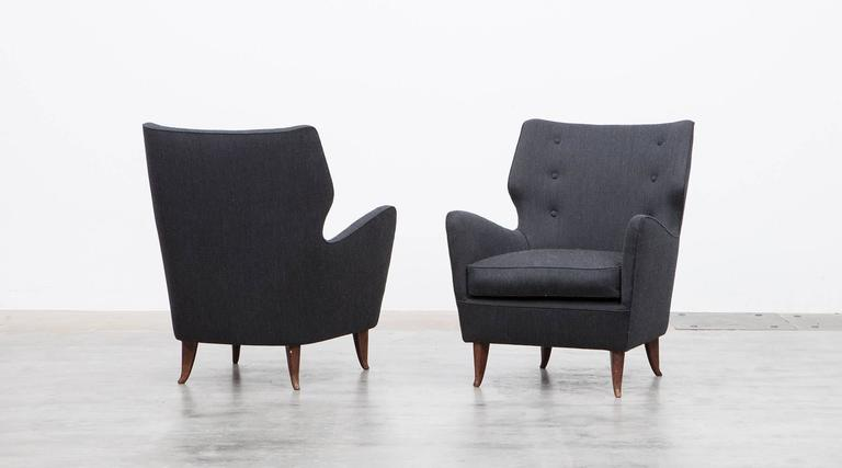 A pair of lounge chairs designed by Gio Ponti. Its sensual curves and the elegantly tapered legs give the chairs a sculptural and modern look and feel. These sumptuous lounge chairs are in good condition and comes in high-quality fabric.