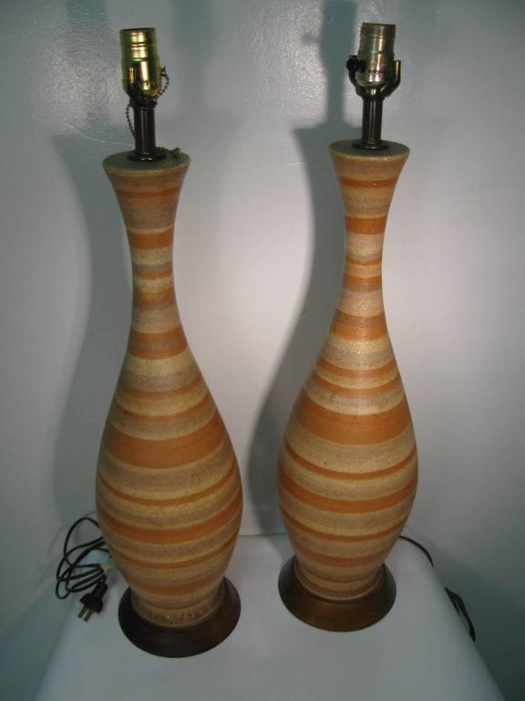 Beautiful and well-crafted pottery lamps. Earth tone colors with walnut plinth bases.