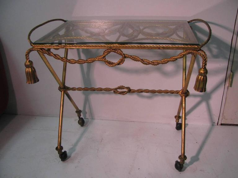 Beautiful and elegant gilt rope and tassel bar cart from Italy. 'X' stretcher frame unique in its design.