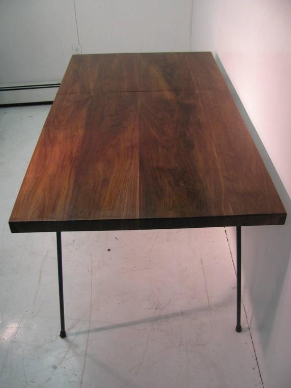 Beautiful and newly created black walnut top with leaf. Figural walnut grain with the leaf also. Walnut sits atop original black iron base. 1.5 inch apron surrounds the edge of the table. Leaf is one foot wide. Table is 42 in. without the leaf.