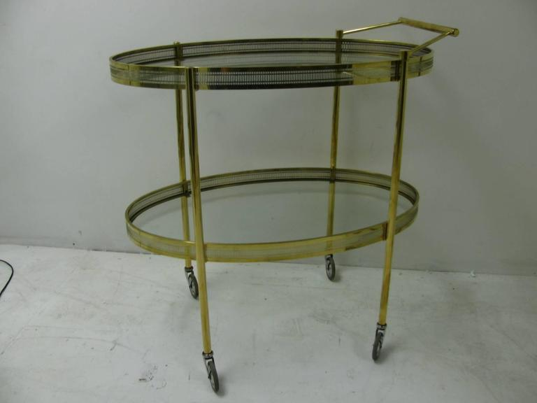 Simple and elegant brass bar cart with pierced apron and oval glass shelves. Chrome with rubber tires provide a quiet easy glide across the room. Top glass shelf is 30 x 18 with a height of 28 in. from the floor.
