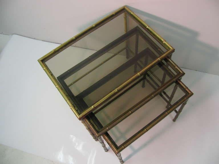 Set of three solid brass nesting tables with original glass tops. Created in the faux bamboo style, tables are stamped made in Italy. Brass has tarnished. Brass polishing available.