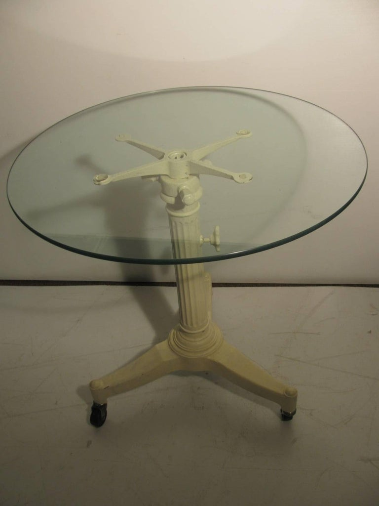 Cast iron medical table base, which is adjustable in height, re-purposed as a cafe table or a end table. Round 3/8 inch thick glass. Lowest height is 26 inches. Caster wheels may be removed.