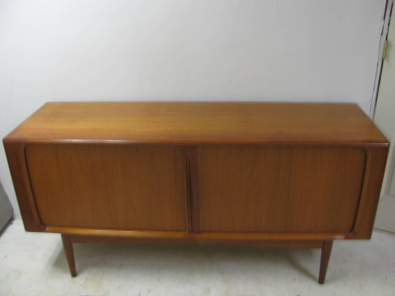 Simple and elegant Danish teak credenza cabinet with tamboor doors. Great size with plenty of storage. Doors glide effortlessly. Three flatware napkin drawers center the piece while the sides each have shelves with openings. Opening with shelving