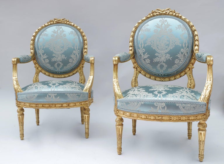 Pair of Louis XVI style giltwood armchairs with a flat backrest in a medallion shape. They rest on four legs with fluted shafts. The giltwood is carved with decoration of ribbons, garlands of laurel wreaths and acanthus leaves, in the classical