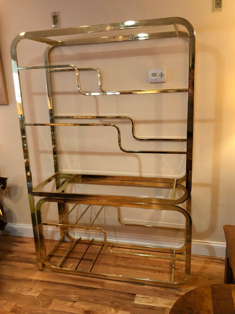 Milo Baughman Design Institute Of America brass and glass etagere. Glass shelves line this brass beauty. Lower adjustable section which slides out. Signed Design Institute of America.