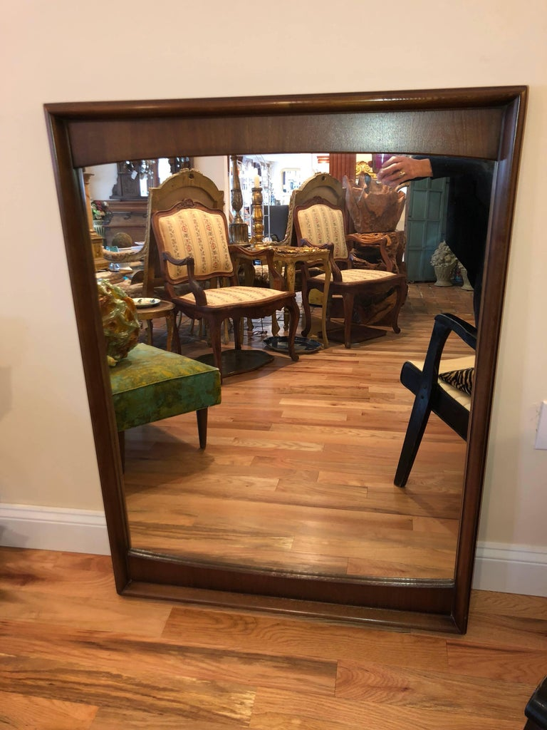 Mid-Century Modern walnut mirror. Somewhat bow-tie shaped, this mirror would look great over any mid-century table, dresser or in a bathroom. Reduced for clearance