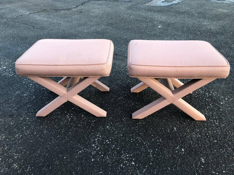 Pair of X-base stools or ottomans in the style of Billy Baldwin. Pale pinkish mauve upholstery. Could use a recover. Some marks on stools. See photos. Hollywood Regency design but of the midcentury period.