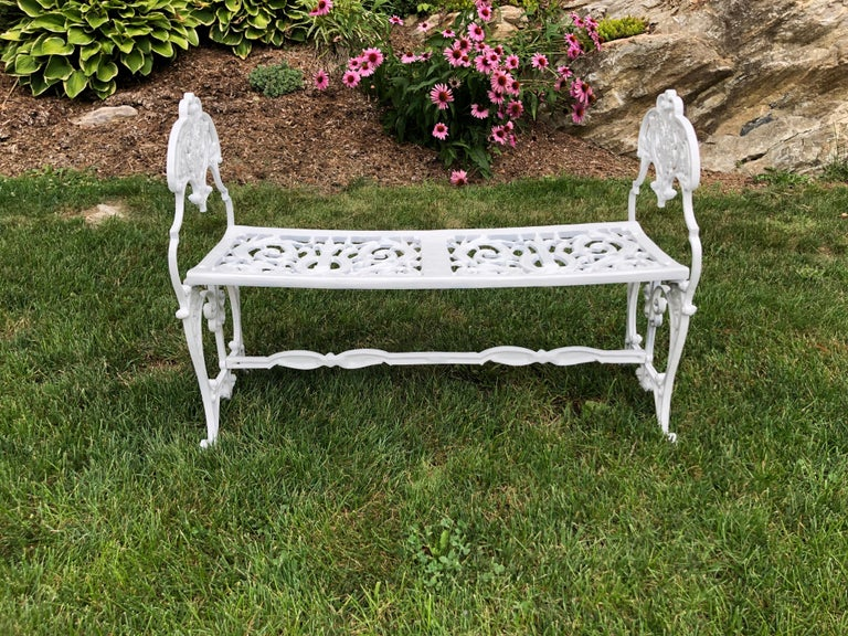 Neoclassical white garden bench. Perfect size to move easily around your garden. Petite and highly decorative with all of its scrolls and embellishments. Recently refinished and repainted. Love seat size, Ideal for two.