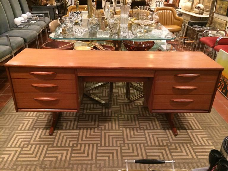 Danish Mid-Century Modern Floating teak desk or vanity. Made up of seven drawers. The center drawer is exceptionally deep with a recessed lower tier.Great for office or dressing room.