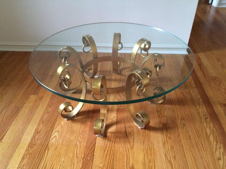 Hollywood Regency gilt iron coffee table. This elegant table boasts a 40 inch ; round glass top that has an impressive 3/4 inch thickness. In excellent condition.