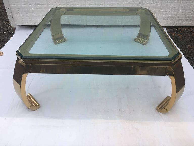 Asian inspired brass coffee table. This classic beauty is made of solid forged brass. It is the epitome of 1970s sexy chic. The 3/4 inch beveled glass top sits on top of the base, unattached. The thick curved Ming style legs on this piece are