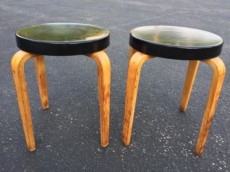Pair of authentic Thonet stacking stool tables. Classic black hard plastic top with bentwood legs. Signed Thonet underneath. One stool table has a slight 6