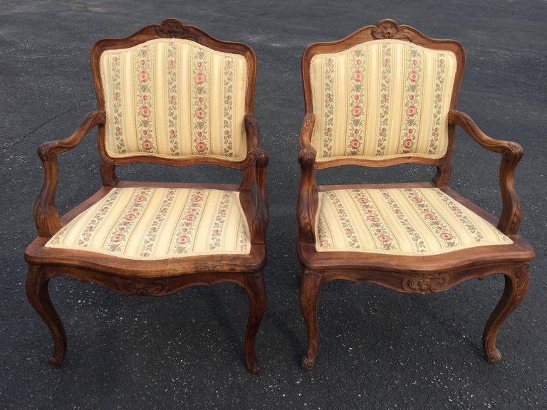 Pair of French Louis XV style armchairs. Nicely carved pair with nice patina. Upholstery in excellent condition. They will accentuate any French country home.