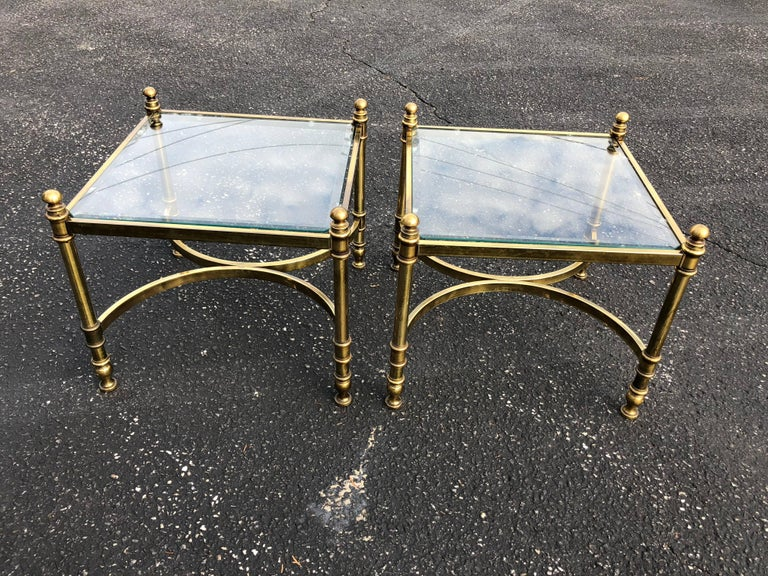 Pair of Hollywood Regency brass and glass end tables. Glass tops are removable and have a nice one inch bevel all around. They are cut in a hexagonal pattern.