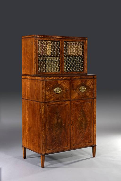 George III Sheraton period 18th century satinwood inlaid secrétaire dwarf bookcase.   The inlaid and crossbanded satinwood two-door bookcase above a secrétaire chest is fitted with lozenge-shaped gilt-brass grills, glass panels and a mahogany
