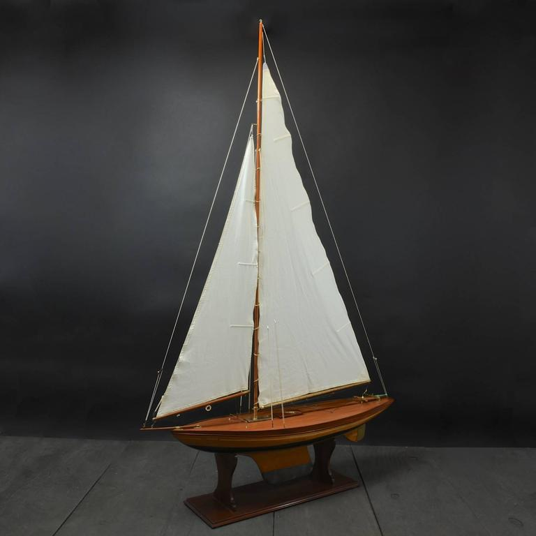 An elegant Bermudian rigged pond yacht named 'Grace', circa 1935. Constructed with a part painted plank on frame hull, beautifully curved planked deck, brass rudder and a lead keel. The model utilizes a balanced main sail method of steering. The