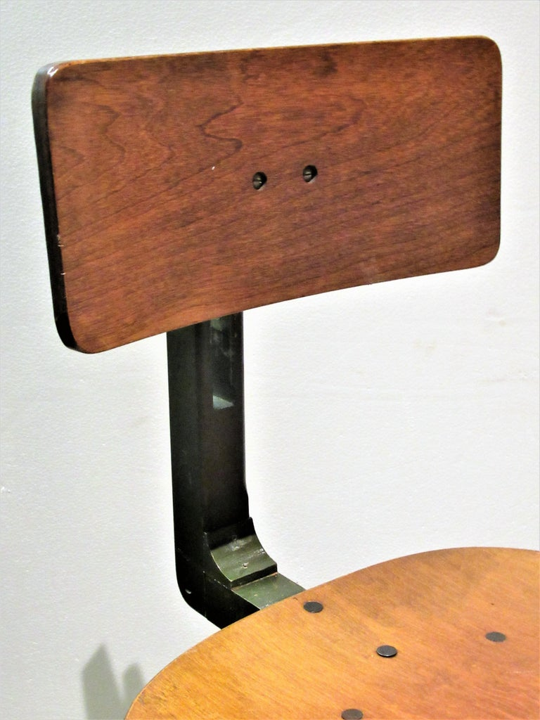 A unusual and hand hard to find American industrial modernist patented stool having both adjustable height and backrest positions in all original beautifully aged painted and natural laminated wood and metal surface with a great looking