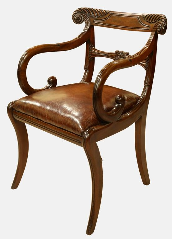 A fine pair of Regency period carved mahogany carver chairs of trafalagan back design with leather seats.