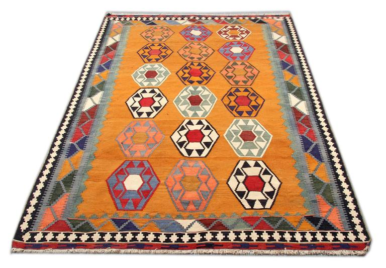 A sensational antique Qashqai Kilim, which is a tribal rug and a flat-weave rug with excellent saturated natural dyes and great geometric rug pattern. This goldish yellow rug has repeating patterns all-over and the colorful border of the carpet rug