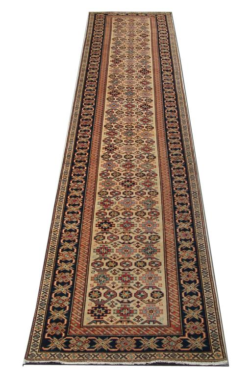 This new traditional hand-woven rug is an example of a geometric rug that comes in a striking color combination. The bright red, green, navy, dark blue, sea blue, ivory, and caramel colors look magnificent with this elegant cream rug. The border of