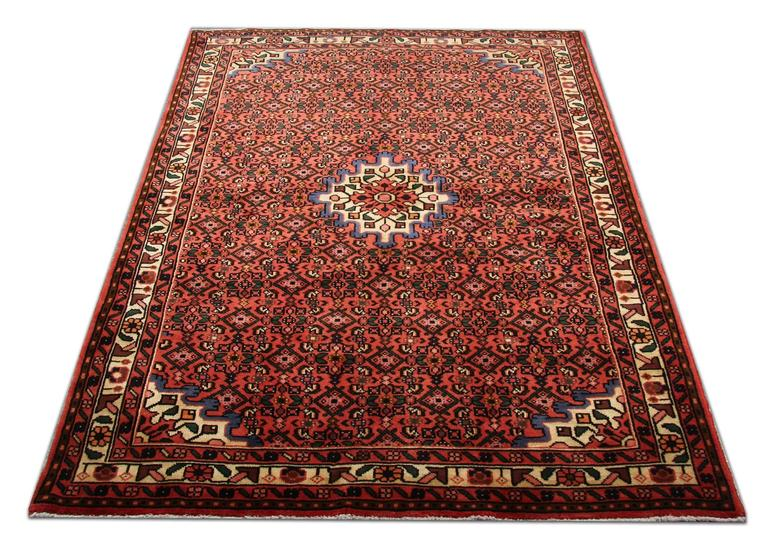 This Old Persian floral rug from Hamedan is in excellent condition. This red rug has a beautiful small medallion, which stands out with its cream color and matches the borders of this carpet rug. This woven rug has brown, red, purple, orange and