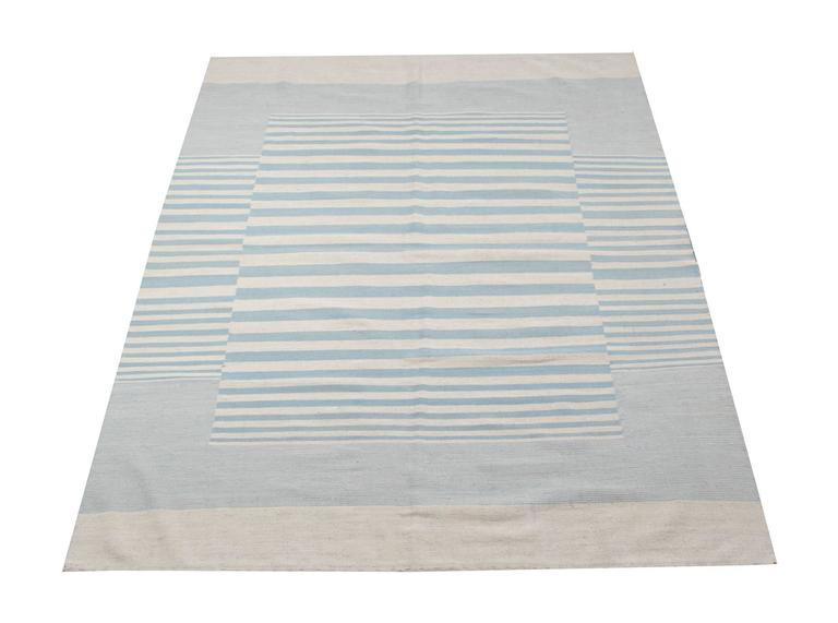 This striped rug is 100% handmade in Afghanistan. Kilim rugs are flat woven. The materials used for these handmade rugs are wool and cotton. Only organic dyes were used for these luxury rugs. This light blue rug is hard-wearing and therefore will
