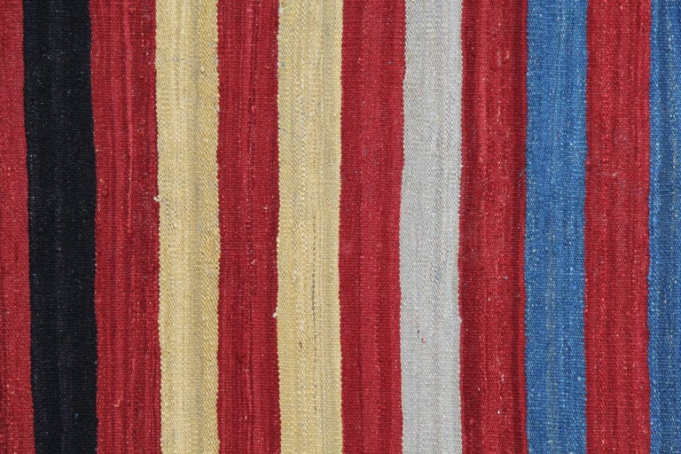 These are colorful kilims from Afghan. This modern carpet is composed of stripes in red, yellow, blue, green and black in color. This striped rug has a very bold color for a very fine texture. These contemporary rugs are a very effective way do