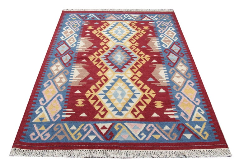 This deep red rug is a flat-weave rug woven in stylish colors. This geometric rug has an elegant soft blue border and the rest of the colors that we can see on this tribal rug are red, yellow, white and pink. These colorful Indian rugs would