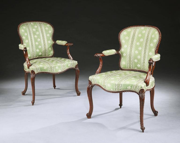 An exceptional set of four George III armchairs in the French Hepplewhite taste, attributed to John Cobb. The mahogany show frames of exceptional depth of colour and magnificently carved throughout with gadrooned detail. With silk upholstered backs,