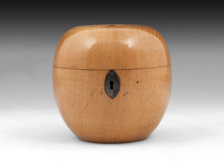Antique treen apple tea caddy with lovely blonde colour, has button stalk and oval cut steel escutcheon.   This treen apple tea caddy still has traces of its original tin foil lining, comes with a fully working lock and tasselled key, has
