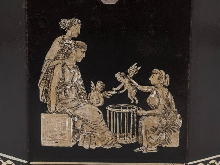Octagonal papier mâché tea caddy, decorated with classical figures and cherubs. Entwined diaper borders which are also repeated on the hinged, silvered-handled top. 