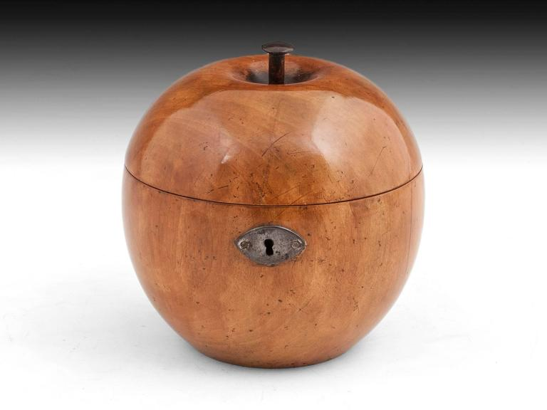A George III fruit wood apple tea caddy with a wonderful colour and original button stalk, steel lock and escutcheon. The interior of this treen apple still has traces of its original lining.  This lovely shaped apple tea caddy comes with a fully