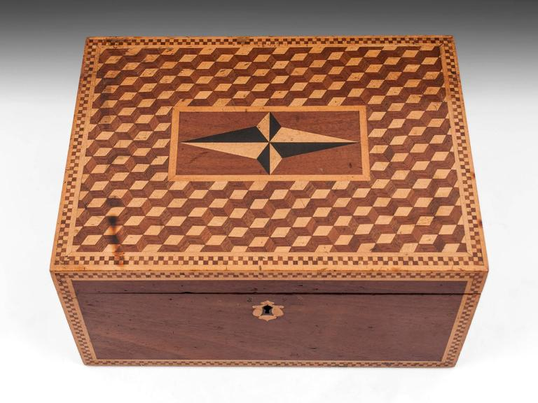 Antique box made of mahogany with an interesting cube perspective design on the top with a four point nautical star in the center.  The interior is lined with black leather paper and purple velvet.  The exterior shows signs of age and has one or