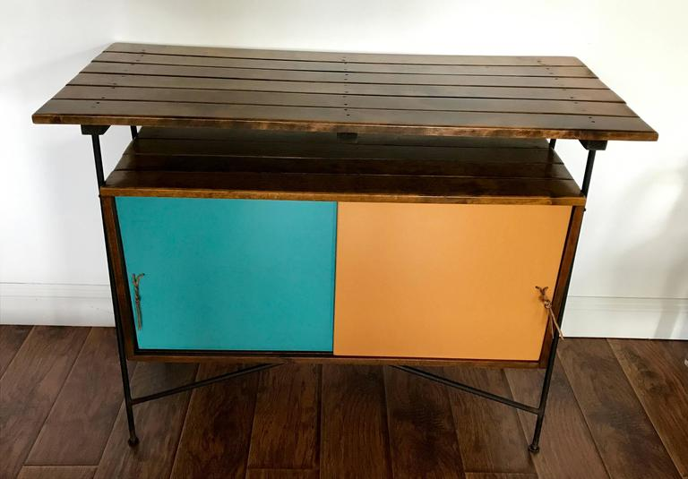 Very cool piece by Arthur Umanoff, can be used as a bar, sideboard, foyer table or server. Umanoff's signature style consisting of slat wood, wrought iron and laminate. Leather pulls for sliding doors. Back is finished in white laminate. All