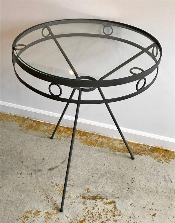 Very cool 1950s metal side tables or cafe tables with tripod legs and round ring accents. Freshly painted anodized bronze. Indoor/ outdoor. Minor surface scratches on glass tops.
