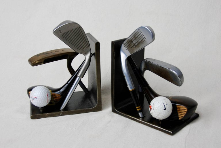 Vintage golf club heads made into bookends by American artist Breck Armstrong. Club heads attached to heavy steel base.