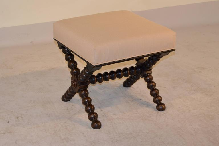 19th century English oak stool with X-stretcher legs, which have been hand-turned in a spool pattern. Newly upholstered in linen and finished with a single welt.