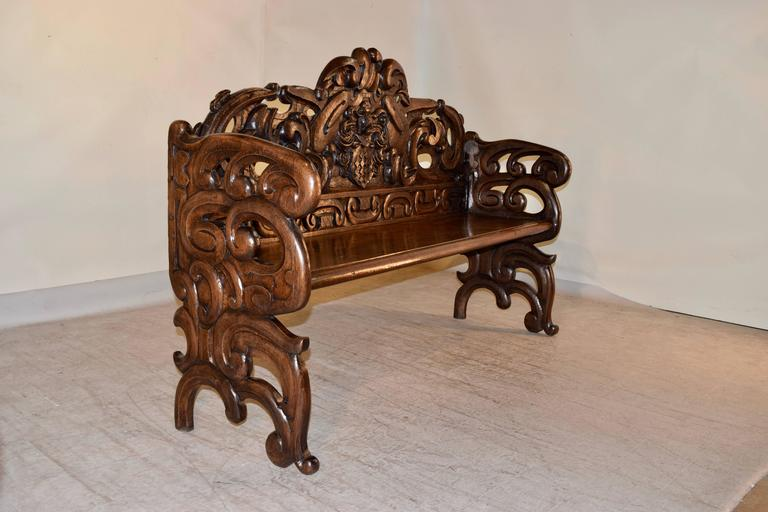 19th century French bench made from oak. The back is exquisitely hand-carved with a central coat of arms, surrounded by decorative carvings. The sides are made up of matching decorative pierced carvings. The seat has a beveled front edge, and the