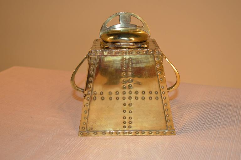 Late 19th century brass inkwell. The top lifts to reveal a porcelain inkwell. The base is detailed with rivets and on the front has a horses profile surrounded by a horseshoe, with a pen rest below.